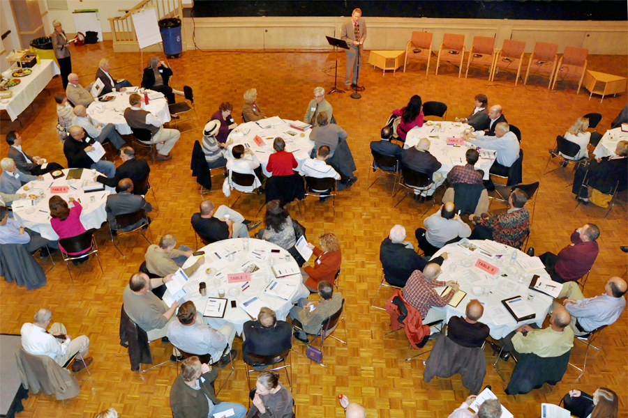 Large meeting with people at round tables