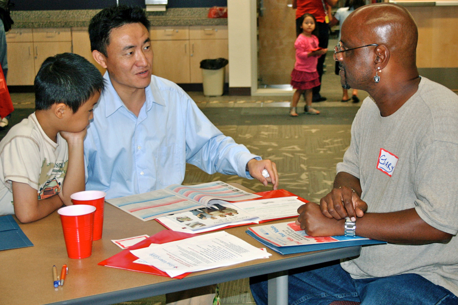 Father and son talk to a volunteer at the library